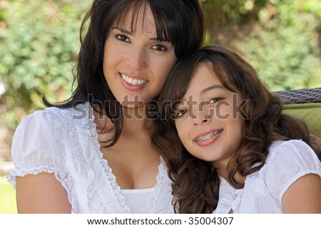 pretty woman sits outside with her cute daughter.