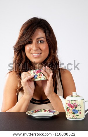 Pretty woman sitting and enjoying a cup of soothing tea from a flowered tea cup. - stock photo