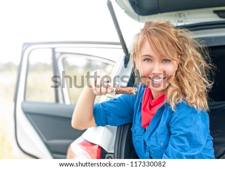 Pretty woman sitting in trunk and smiling. Portrait of young girl with beautiful hairstyle holding chocolate bar. White car with open doors and happy blonde looking into camera. Outdoor eating. - stock photo
