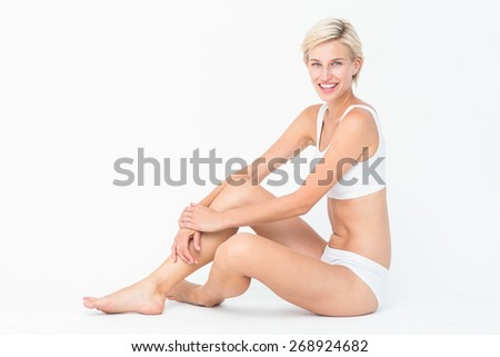 Pretty woman sitting on the floor smiling at the camera on white background