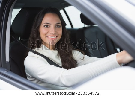 Pretty woman smiling and driving in her car - stock photo