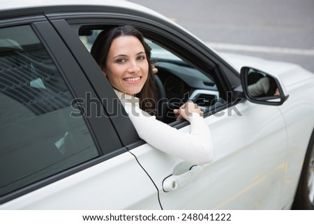 Pretty woman smiling at camera in her car - stock photo