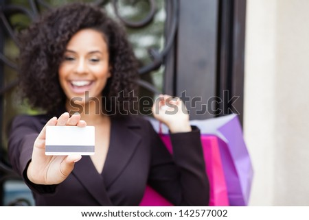 Pretty woman smiling holding a credit card focus is on the card - stock photo