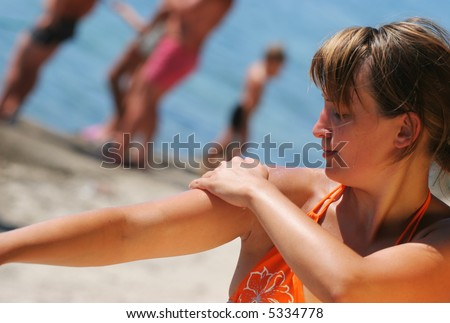 Pretty woman smooth her skin wit suntan lotion - stock photo