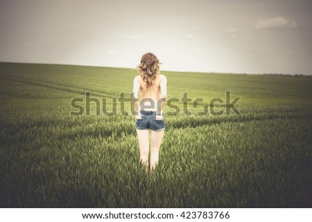 pretty woman standing half naked in a field / woman in a field - stock photo