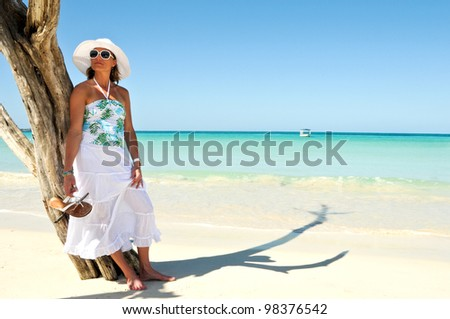 Pretty Woman standing on a white sand beach of a paradise island - stock photo