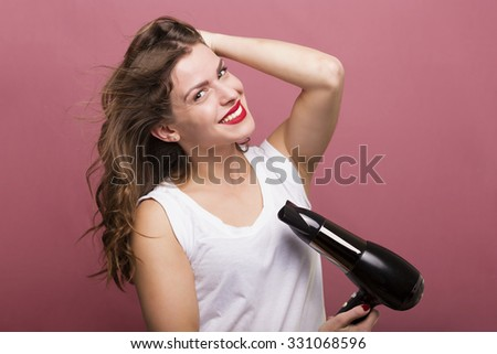 Pretty woman styling her hair with a hairdryer - stock photo