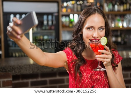 Pretty woman taking a selfie with her cocktail in a pub