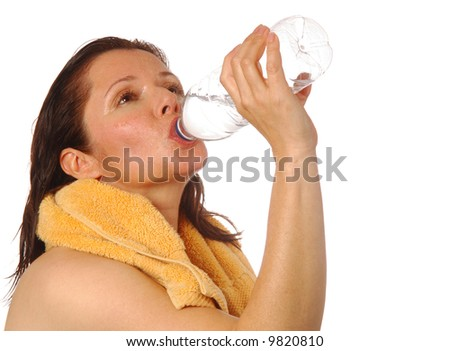 Pretty woman taking a swig of bottled water after a workout - stock photo