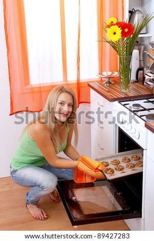 Pretty woman taking the cookies out of the oven