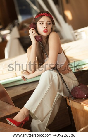 pretty woman talking on old telephone. Fashion model. Red lips. Sunny color. - stock photo