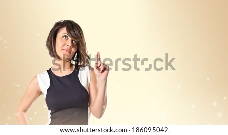 Pretty woman thinking over ocher background  - stock photo