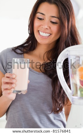 Pretty woman using a blender while holding a drink in the kitchen - stock photo