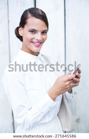 Pretty woman using her smartphone in front of wooden grey planks