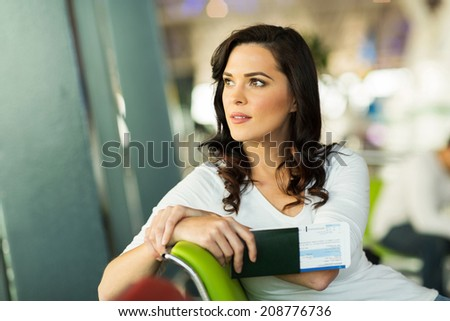 pretty woman waiting for her flight at airport - stock photo
