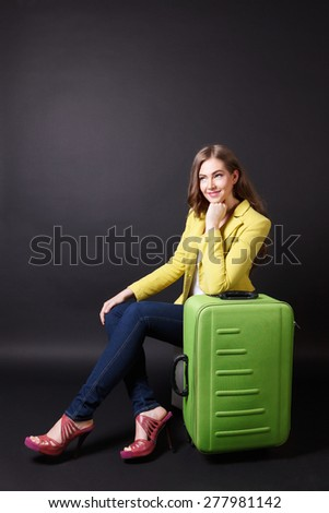 Pretty woman waiting with a big baggage - stock photo