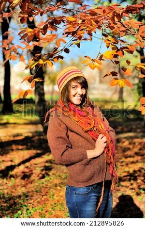 Pretty woman walking outdoor in autumn park.  - stock photo