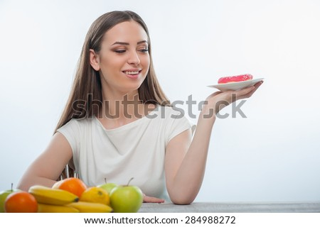 Pretty woman wants to eat unhealthy donut. She is sitting at the table and holding the plate. The lady is smiling. Isolated on a white background  - stock photo