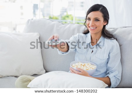 Pretty woman watching tv eating popcorn in her living room - stock photo