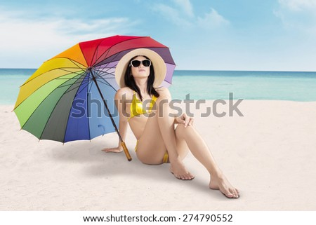 Pretty woman wearing swimwear and sunglasses, sitting on the sand under colorful umbrella at seaside