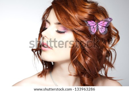pretty woman with a butterfly in her hair - beauty shot - stock photo