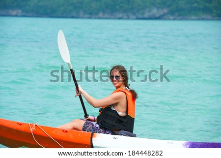 pretty woman with a paddle kayaking on the south sea - stock photo