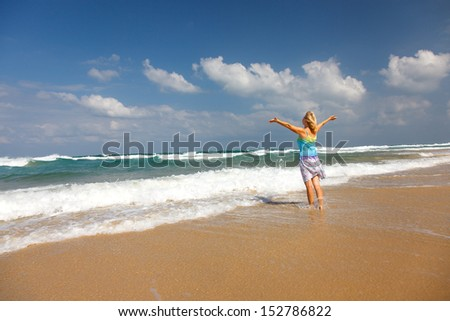 Pretty woman with arms raised  - stock photo