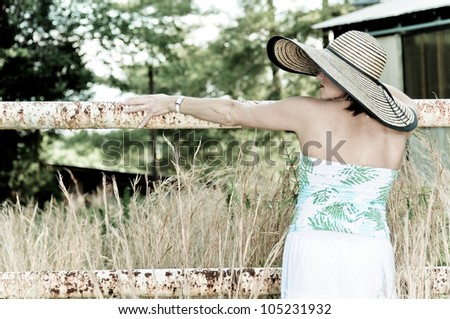 Pretty Woman with big hat leaning on rusted fence. Photo in old color style. - stock photo