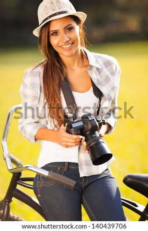 pretty woman with camera sitting on bicycle outdoors