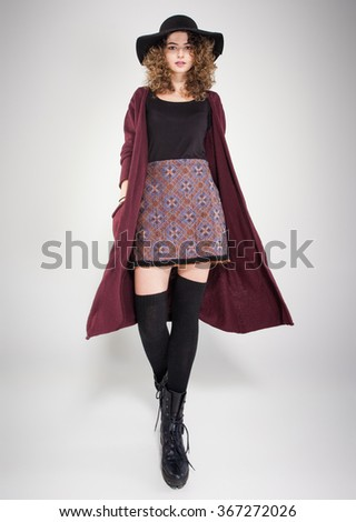 pretty woman with curly hair dressed casual posing in the studio - stock photo