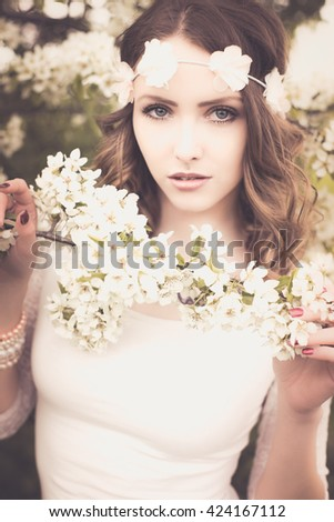 pretty woman with flower hair band in front of a blossoming apple tree / Spring - stock photo