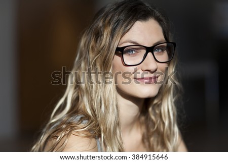 Pretty woman with glasses smiling At the camera