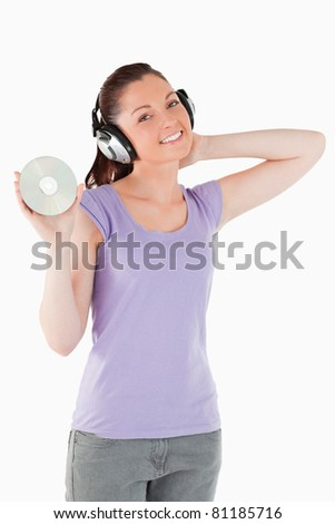 Pretty woman with headphones holding a CD while standing against a white background
