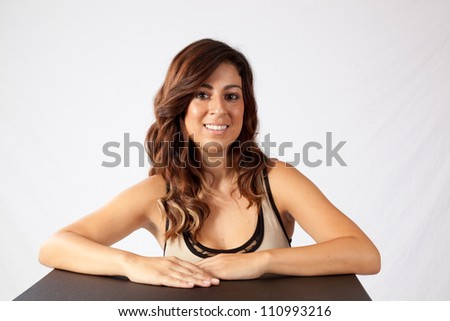 Pretty woman with her arms on a table and looking at the camera with a happy, friendly smile - stock photo