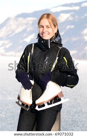 Pretty woman with ice skating schoes at frozen lake - stock photo