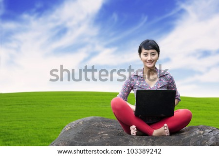 Pretty woman with laptop sitting on the stone shot at green grass background - stock photo