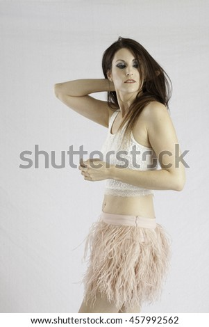 Pretty woman with long hair and her hand in her hair, looking thoughtfully at the camera - stock photo