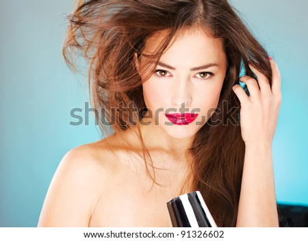pretty woman with long hair holding blow dryer - stock photo