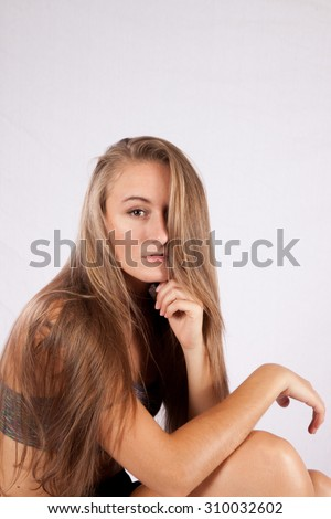 Pretty woman with long hair looking thoughtful - stock photo