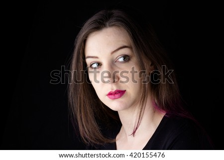 Pretty woman with long rainbow hair against a dark background