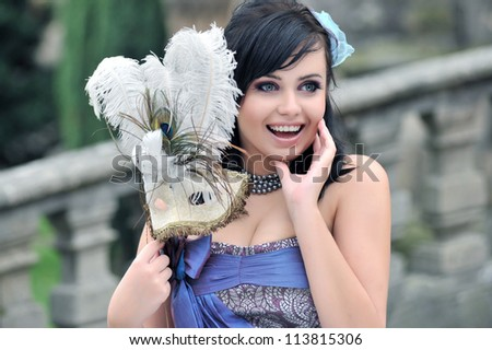 Pretty woman with patterned masquerade mask - stock photo