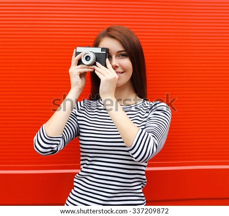 Pretty woman with retro vintage camera in city over red background - stock photo