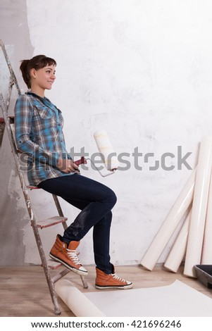 Pretty woman with roller paste wallpaper to repair house - stock photo