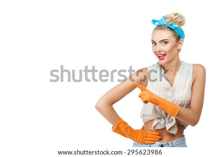 Pretty woman with rubber gloves is pointing her finger sideways. She is smiling and looking at camera with interest. Isolated on background and copy space in left side - stock photo