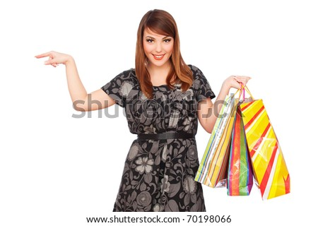pretty woman with shopping bags pointing at something