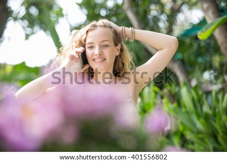 pretty woman with smartphone  using it in garden - stock photo