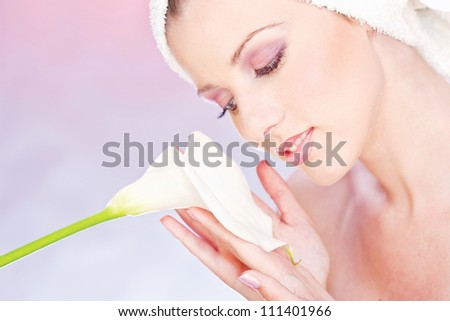 pretty woman with towel on head gently holding a white flower - stock photo