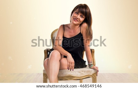 Pretty woman with vintage armchair over ocher background