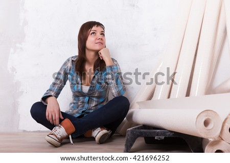 Pretty woman with wallpaper to repair house - stock photo