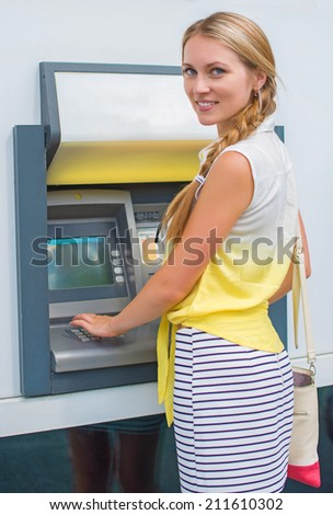 Pretty woman withdrawing money from an ATM. - stock photo